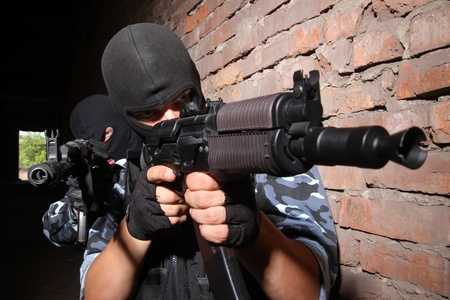 airsoft: Photos of heavy equiped soldiers or terrorists in black masks with automatic guns. Stock Photo