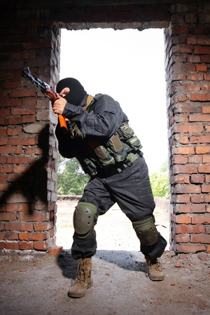 guerrilla: Photos of heavy equiped soldiers or terrorists in black masks with automatic guns. Stock Photo