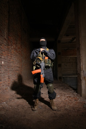 Soldier with automatic AK-47 rifle in black mask and bulletproof vest posing in ruins of urban building photo