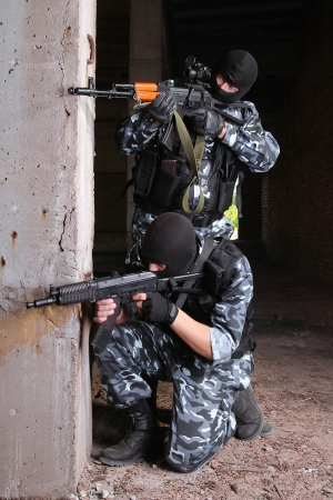 Soldiers or terrorists in black masks and heavy ammunition with automatic rifles photo