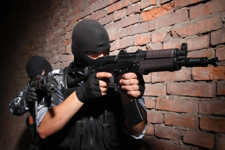 airsoft gun: Soldiers or terrorists in black masks and heavy ammunition with automatic rifles Stock Photo