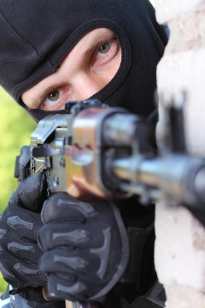 machinegun: Soldiers or terrorists in black masks and heavy ammunition with automatic rifles Stock Photo
