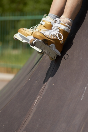inline skater: Legs of inline skater wearing professional aggressive roller skate in a skatepark outdoors  Sitting on a ramp