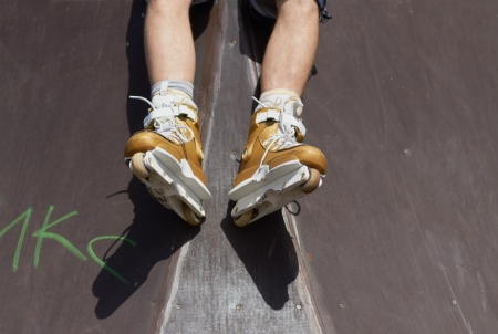 Legs of inline skater wearing professional roller skate in a skatepark outdoors  Sitting on a ramp photo