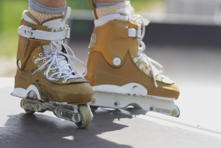 Legs of inline skater wearing professional aggressive roller skate in a skatepark outdoors photo