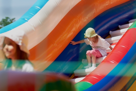 Young girls playing in a bouncing castle in a bright sunny day photo