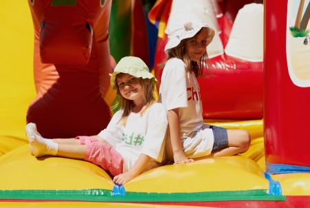 Pretty young girls posing in a bouncing castle in a bright sunny day with beautiful smile