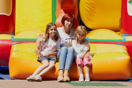 Young loving mother with her cute daughters sitting on the bouncing castle outdoors in a bright sunny day Stock Photo
