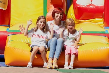 Young loving mother with her cute daughters having fun waving you on a bouncing castle outdoors in a bright sunny day
