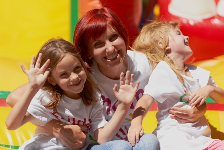 Young mother with her cute daughters waving you laughing on the bouncing castle outdoors in a bright sunny day  Happy family looks just like this  Stock Photo