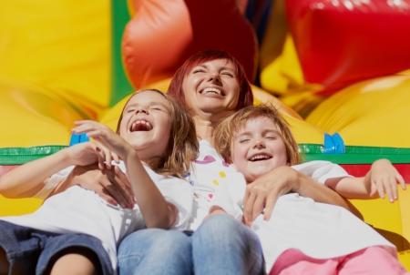 laughing out loud: Mam� y sus hijas por la que se re�a a carcajadas en un castillo hinchable en un brillante d�a de verano al aire libre Lovely day Foto de archivo