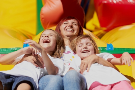 Mom and her daughters laughing out loud laying on a bouncing castle in a bright summer day outdoors  Lovely day  Stock Photo - 14276789