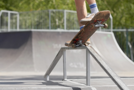 Legs of extreme athlete doing nose grind or 5-0 grind on a square rail on top of fun-box in a skatepark. Dangerous trick! photo