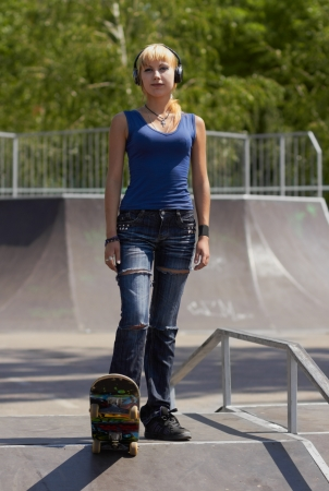 Punk skater chick in torn jeans and wireless headphones ready to roll on her skateboard Stock Photo - 14325334