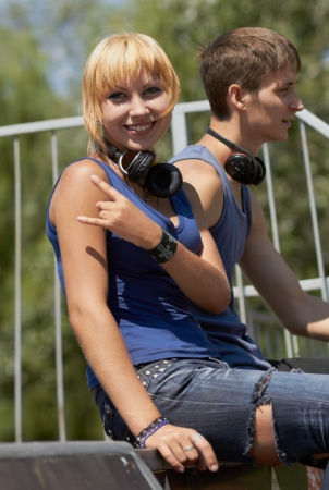 Punk skater chick in torn jeans and wireless headphones sitting on top of quater-pipr in skatepark photo