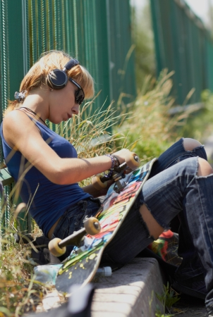 Punk skater chick in torn jeans mounting her board while sitting in trendy wireless headphones outdoors photo