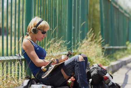 Punk schaatser kuiken in gescheurde jeans montage haar raad van bestuur tijdens de vergadering in de trendy draadloze hoofdtelefoons buiten