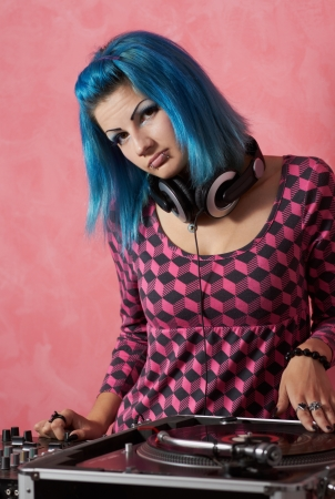 Manga-style punk girl with blue hair playing her music on professional audio equipment Stock Photo
