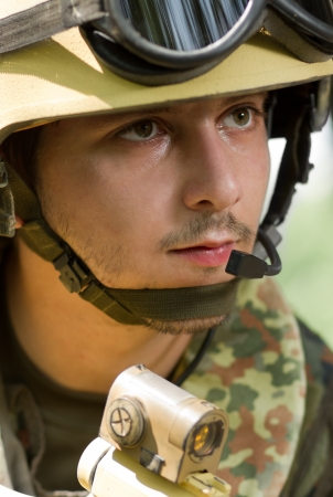Portrait of young soldier in heavy combat ammunition photo