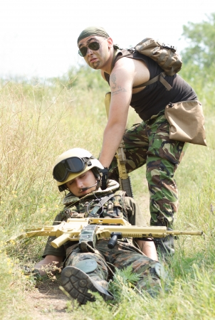 wounded: Brave soldier drags his wounded partner away from the battlefield Stock Photo