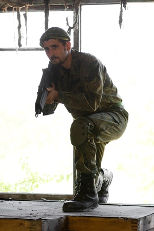 Soldier came into the building through the broken window and now ready to move on Stock Photo - 14633128