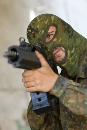 Man in camouflage mask aiming the target with automatic G36 rifle photo