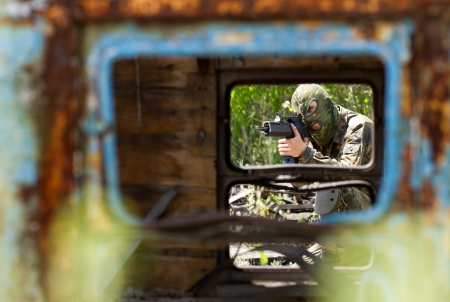 Armed and dangerous  The ruins of a truck will cover him against enemies Stock Photo - 14633133