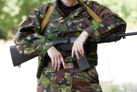 Female soldier with hands on her rifle photo