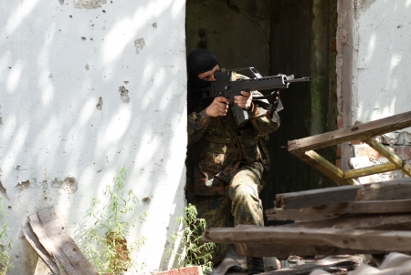 Terrorist defending occupied building with automatic rifle photo