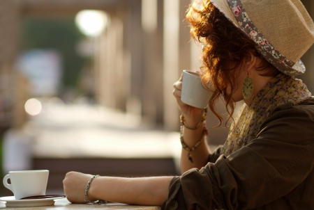 Young girl waiting for somebody in a cafe at sunset photo