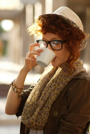 outdoor cafe: Red haired hipster girl enjoying her coffee outdoors Stock Photo