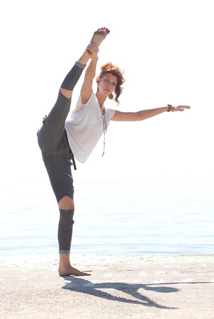 Slim white girl in headphones dancing and doing joga near the sea in a bright summer morning Stock Photo