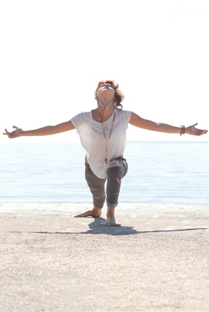 joga: Slim white girl in headphones dancing and doing joga near the sea in a bright summer morning Stock Photo