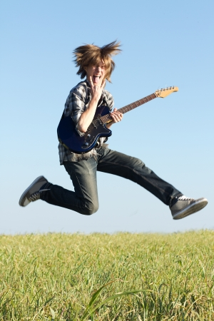 Young rocker posing with musical instrument outdoors at bright summer day