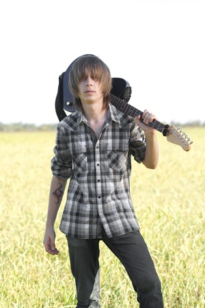 Young rocker posing with musical instrument outdoors at bright summer day photo
