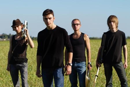 musicos: Serios j�venes rockeros posando con instrumentos al aire libre