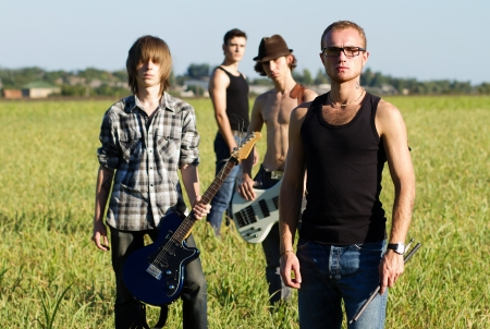 Serious young rockers posing with instruments outdoors