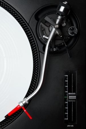 Professional DJ audio equipment - turntable needle on white vinyl record shot from above