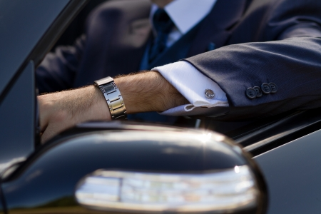 cufflinks: Posh cufflinks on his shirt, expensive watch on his arm, power in his hands