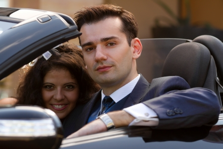 Beautiful young couple sitting in cabrio car outdoors photo