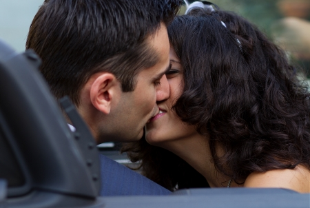 The sweetest kiss in cabrio after their wedding photo