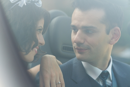 Young husband and wife sitting in a car after the wedding photo