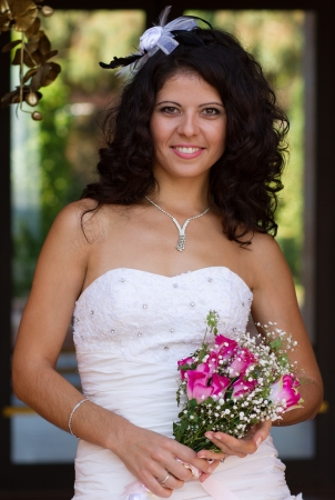 Beautiful young bride holding her wedding bouquet photo