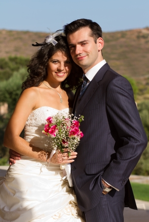Happy newlyweds posing outdoors with their wedding bouquet Stock Photo - 15980714