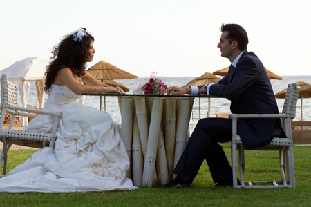Happy newlyweds sitting at the table outdoors at some beach Stock Photo - 15980726
