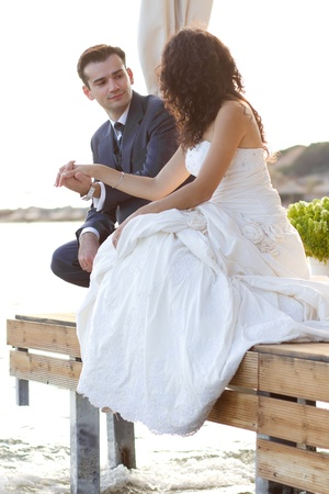 Happy newlyweds sitting at the water looking at each other with love and affection photo