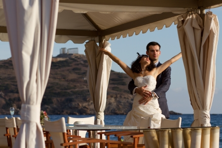 Young couple posing at the sea after their wedding ceremony in Cape Sounio with Temple of Poseidon on the background photo