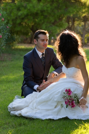 Happy newlyweds sitting in green park at sunset Stock Photo - 15980743