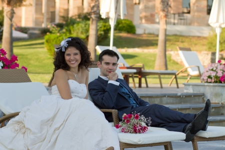 Newlyweds sitting near the pool at some resort at sunset Stock Photo - 15980667
