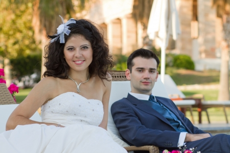 Newlyweds sitting near the pool at some resort at sunset Stock Photo - 15980706